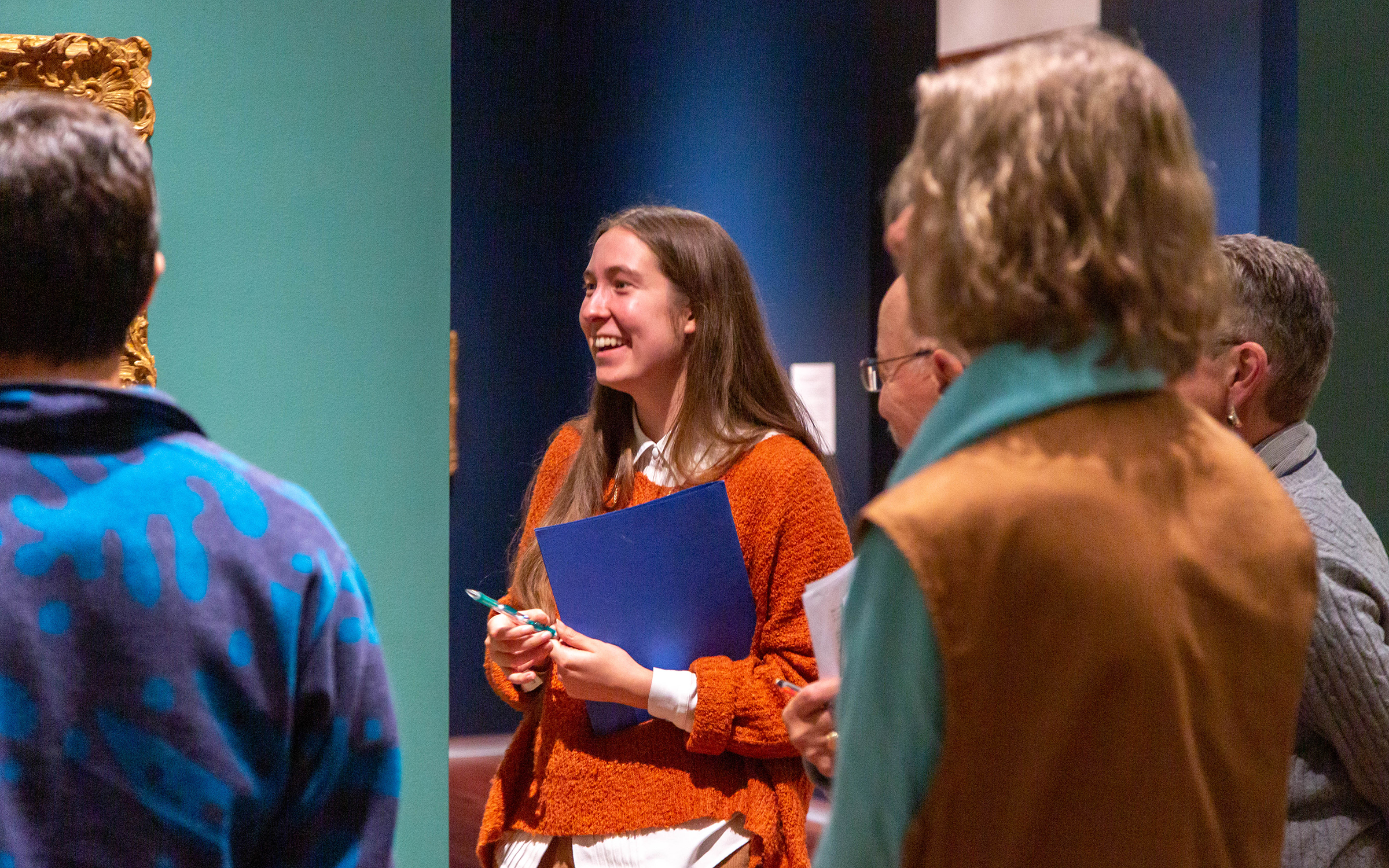 UMFA Art Ambassador training November 2019, women in orange sweater smiles while discussing painting in European Gallery