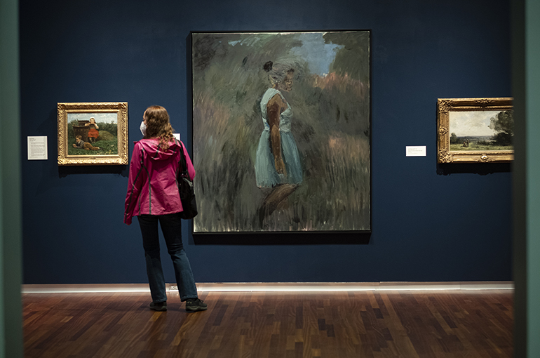 a woman in a pink rain coat stands in the blue walled European galley looking at Lynette Yaidom-Boakye painting