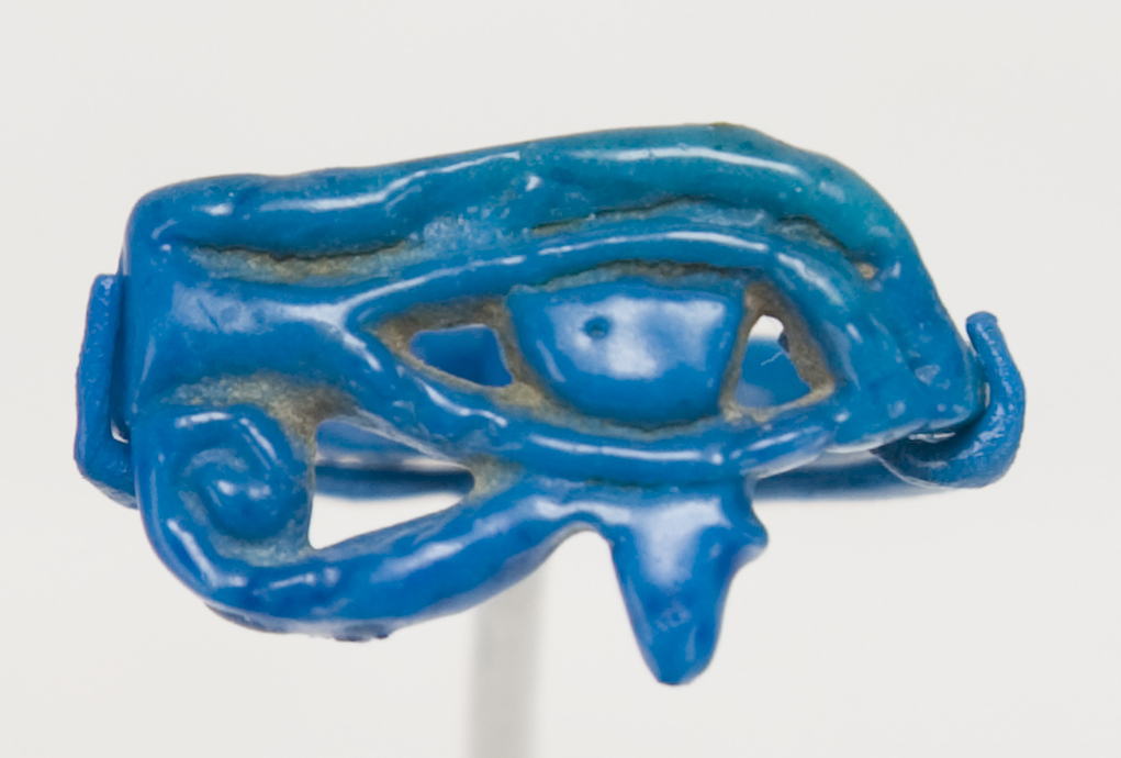 A blue-colored ring carved in the shape of an oval eye with a design in the shape of a spiral below the eye.