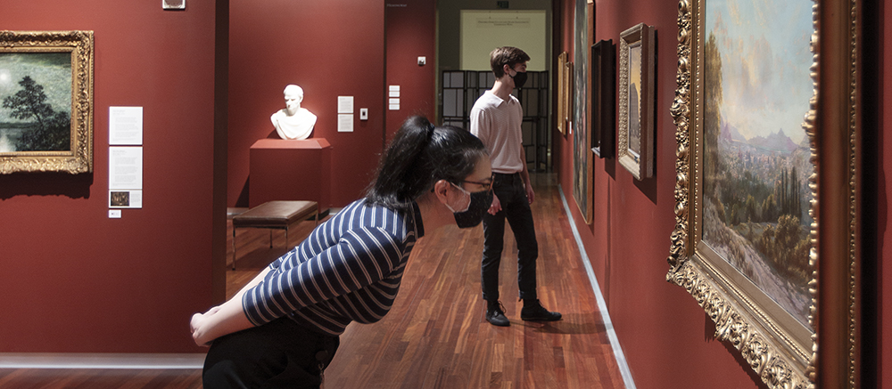 UMFA American gallery, two guests wearing masks look at the art, a woman in a striped shirt in the foreground leans forward to look at art a man stands further down the gallery wearing a white polo and black pants