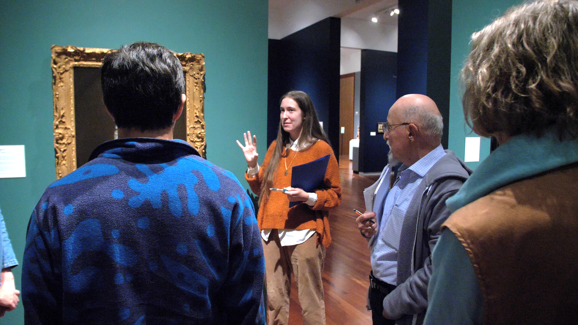 Art Ambassadors tour lead by woman with long hair in orange sweater, three people have the back to camera, European gallery walls are green