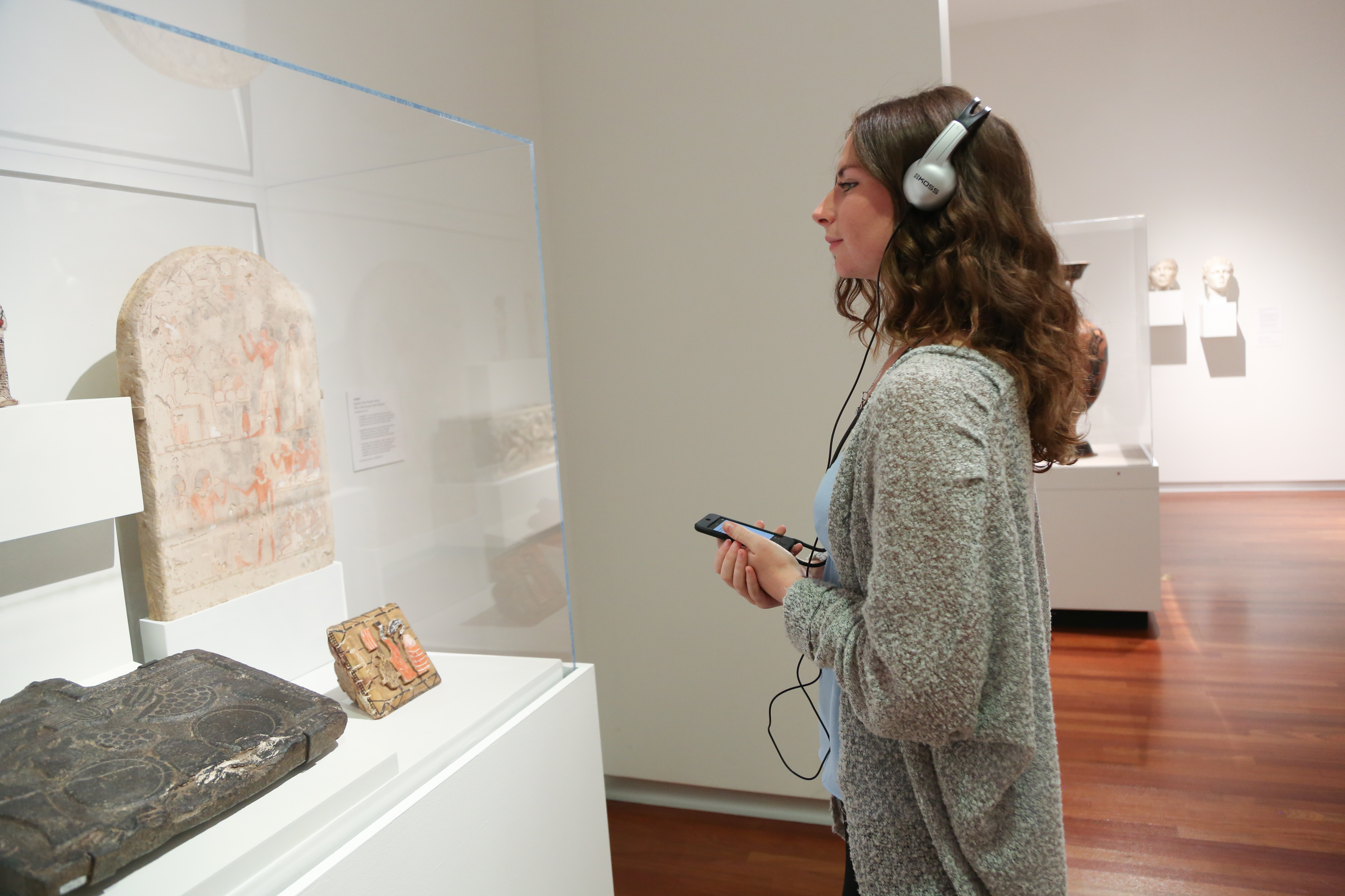 Woman listens to audio about a work of art.