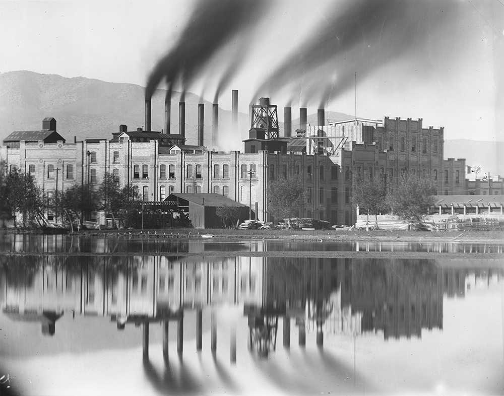 vintage black and whit images of a factory or industrial building with 8 smoke stacks emitting smoke, the building is reflected in a body of water before it