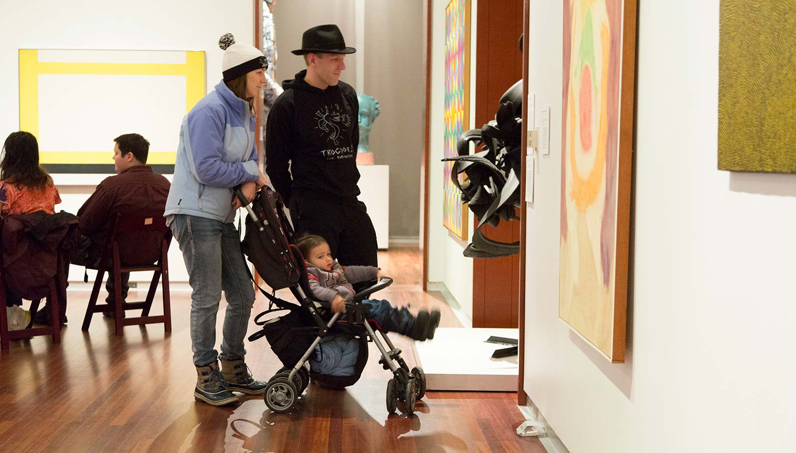 A couple with a child in a stroller view art in the contemporary gallery.