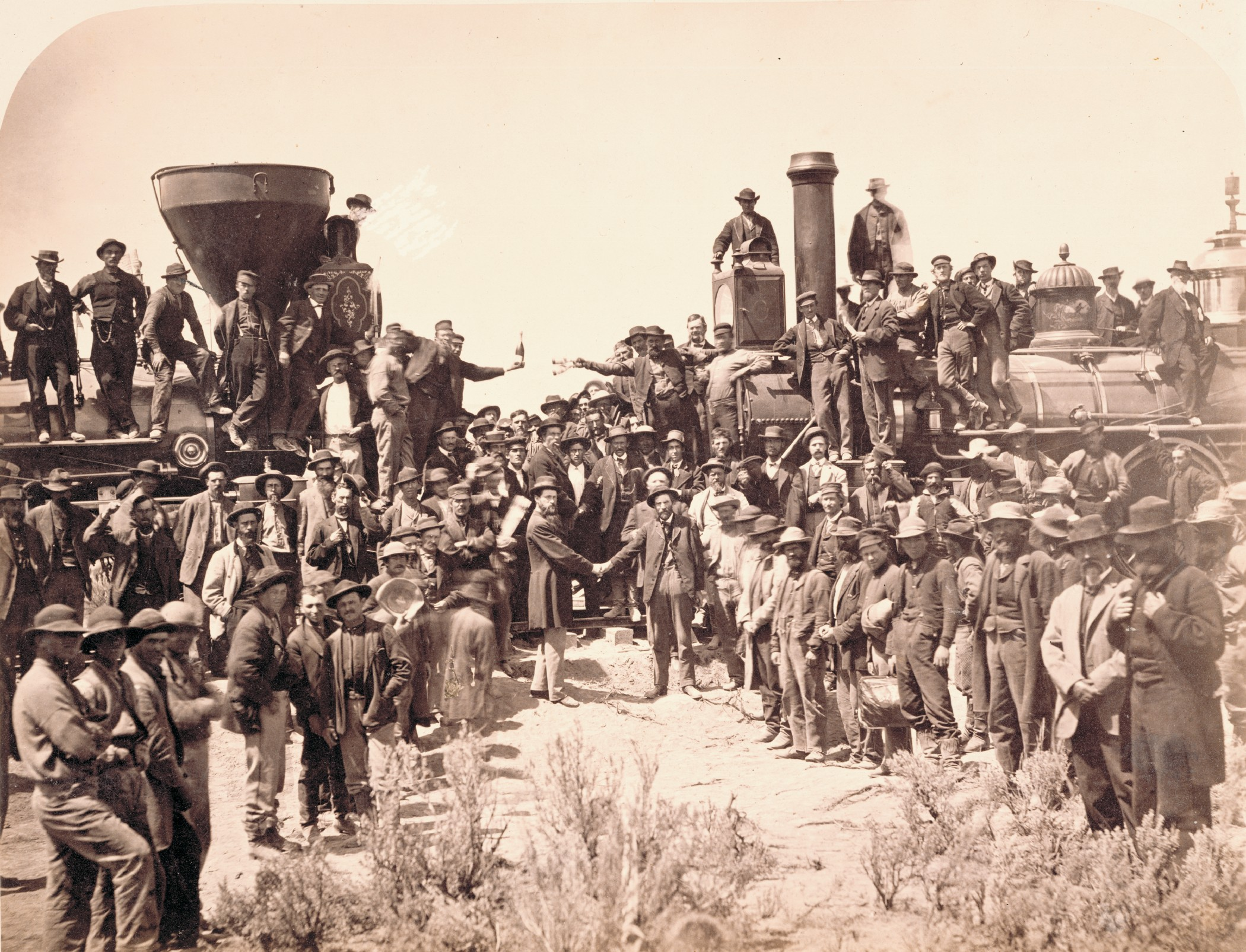 Andrew J. Russell (American, 1830–1902), East and West Shaking Hands at Laying Last Rail, 1869, albumen print,       Courtesy Union Pacific Railroad Museum. The ceremony spotlighted Union Pacific locomotive No. 119 meeting Central Pacific locomotive Jupiter. From left, shaking hands, are Samuel S. Montague, chief engineer of the Central Pacific Railroad, and General Grenville M. Dodge, chief engineer of the Union Pacific Railroad.