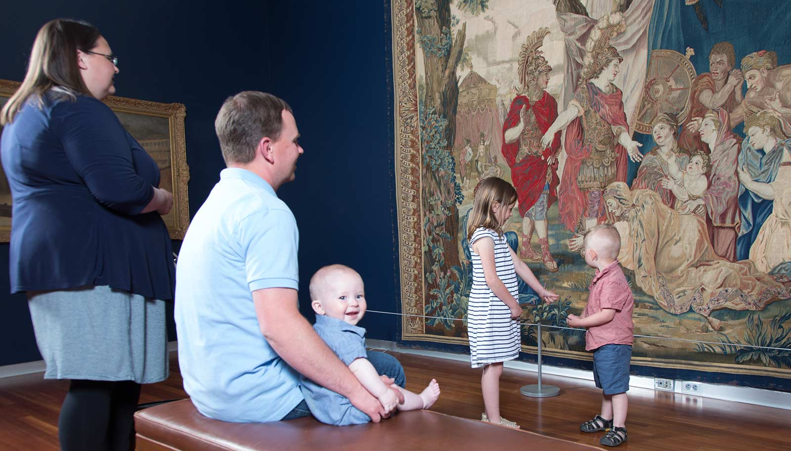 Family with young children viewing art