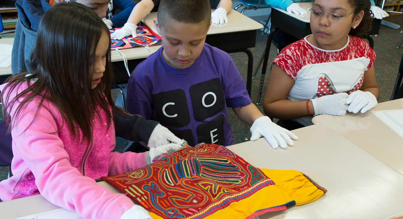 Two students examine an embroidered work of art.