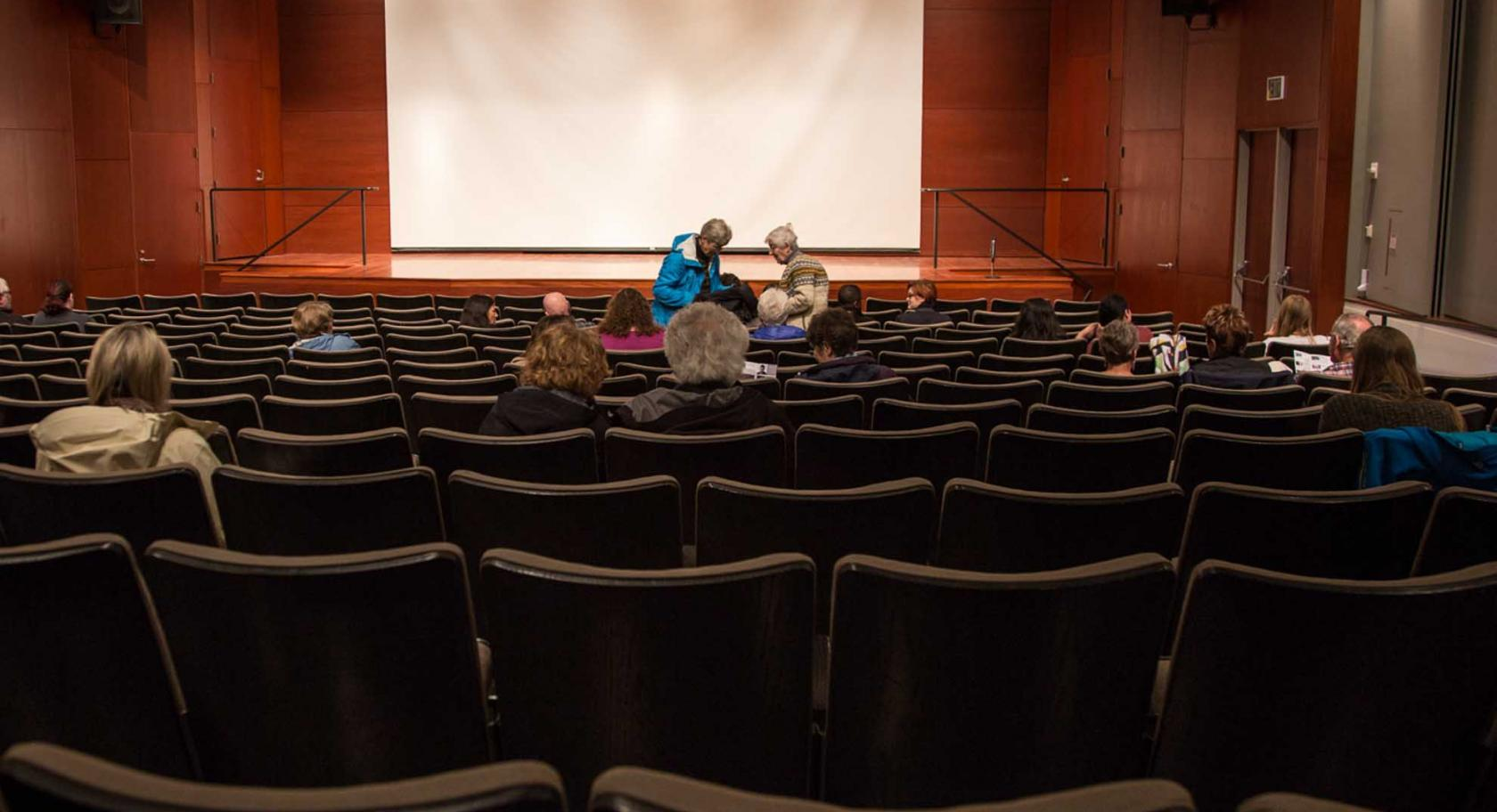 Visitors gathering in auditorium for film screening.
