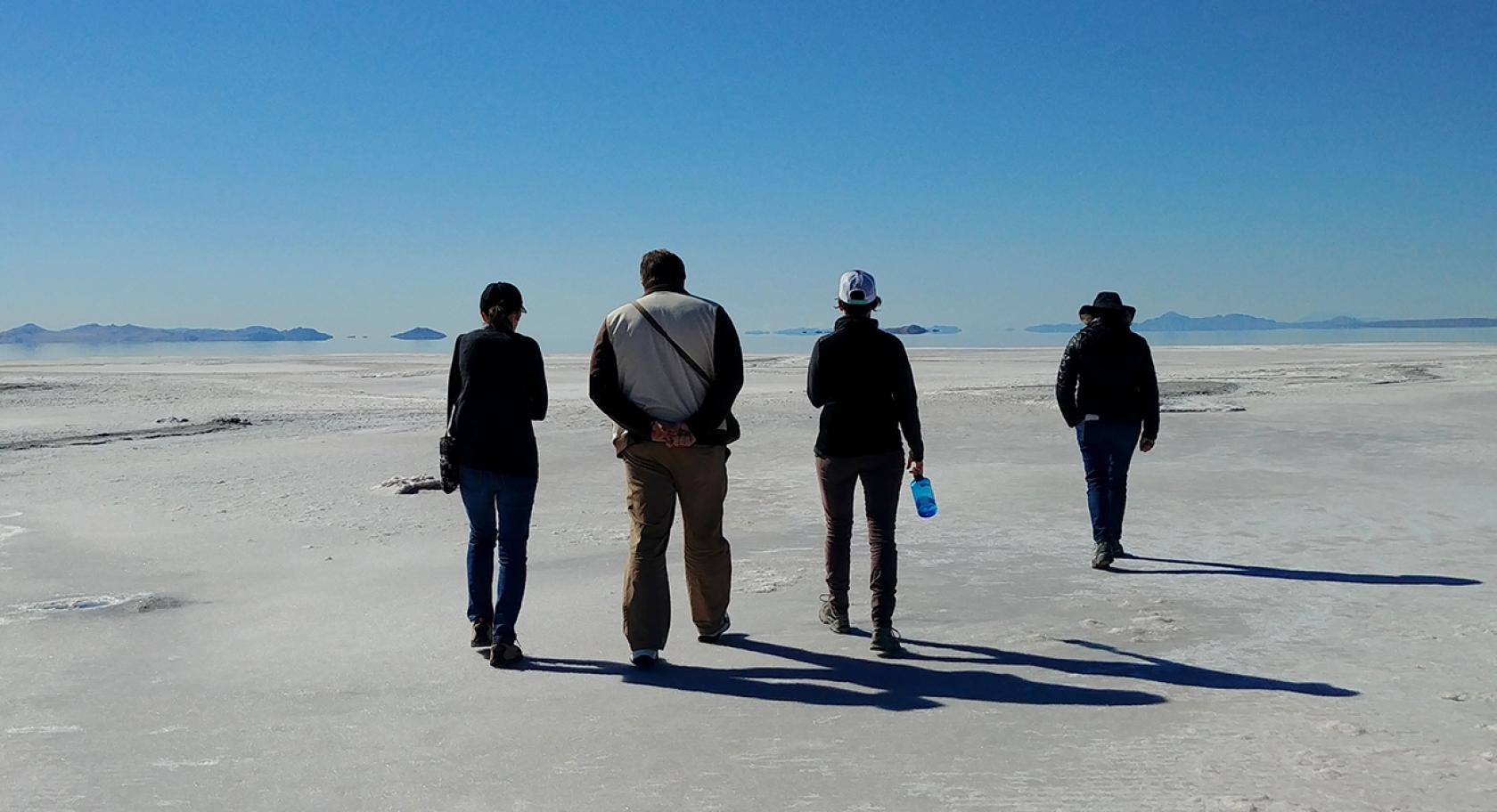 Four people on the shores of the Great Salt Lake walking away from the camera