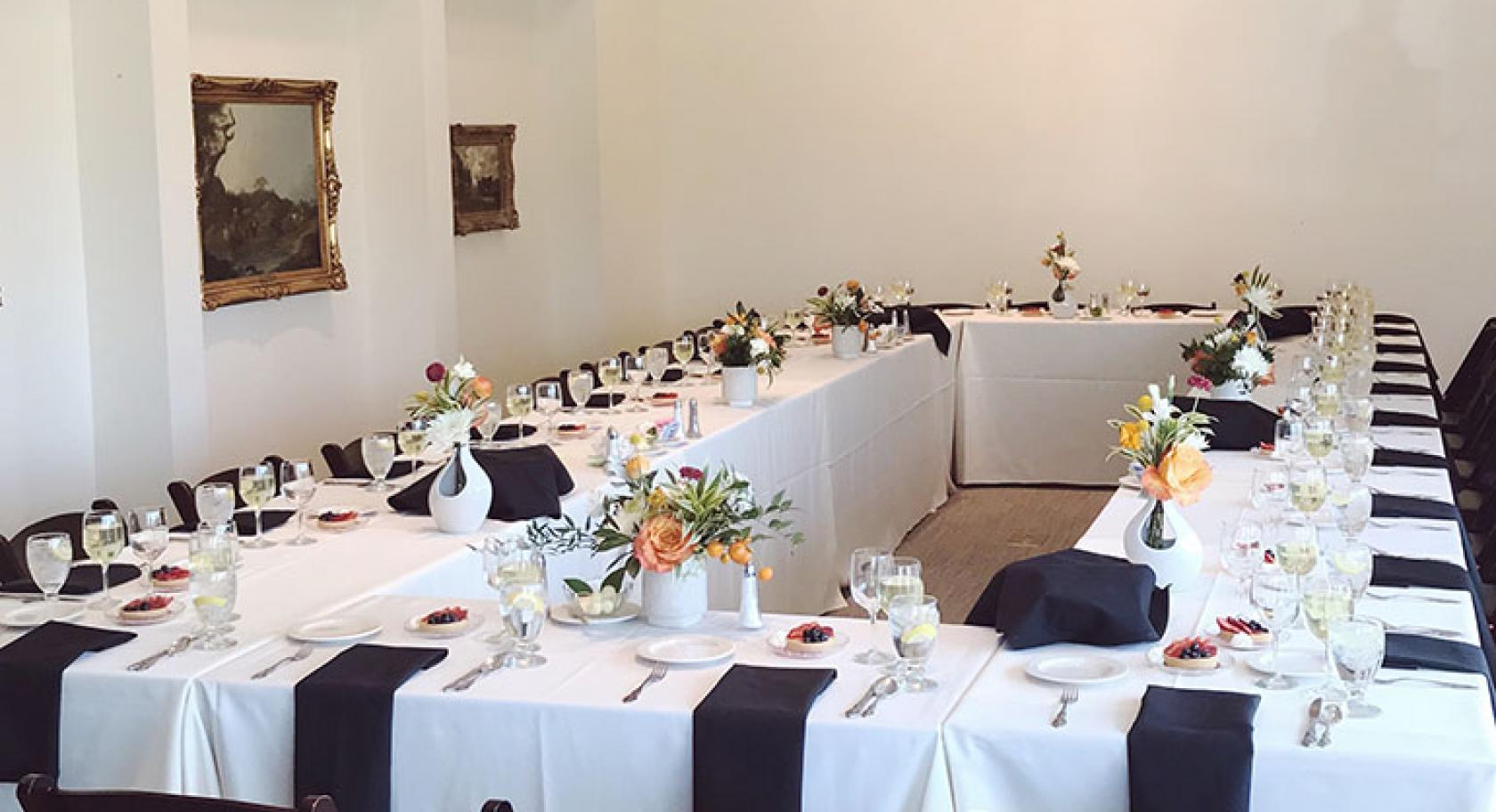 Boardroom meeting space set for dinner flowers full place settings white and black linnens