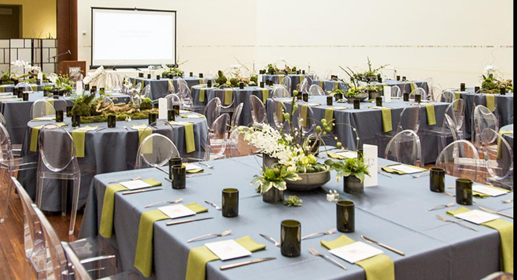 Modern wedding table settings lucite chairs with green and gray linens in the UMFA Great Hall