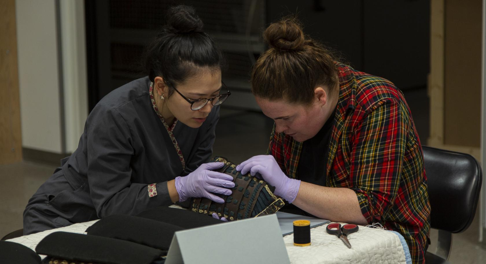 Stacey Kelly and Adelaide Ryder work together to safely attach Ethafoam supports to each panel on the Samurai Armor.