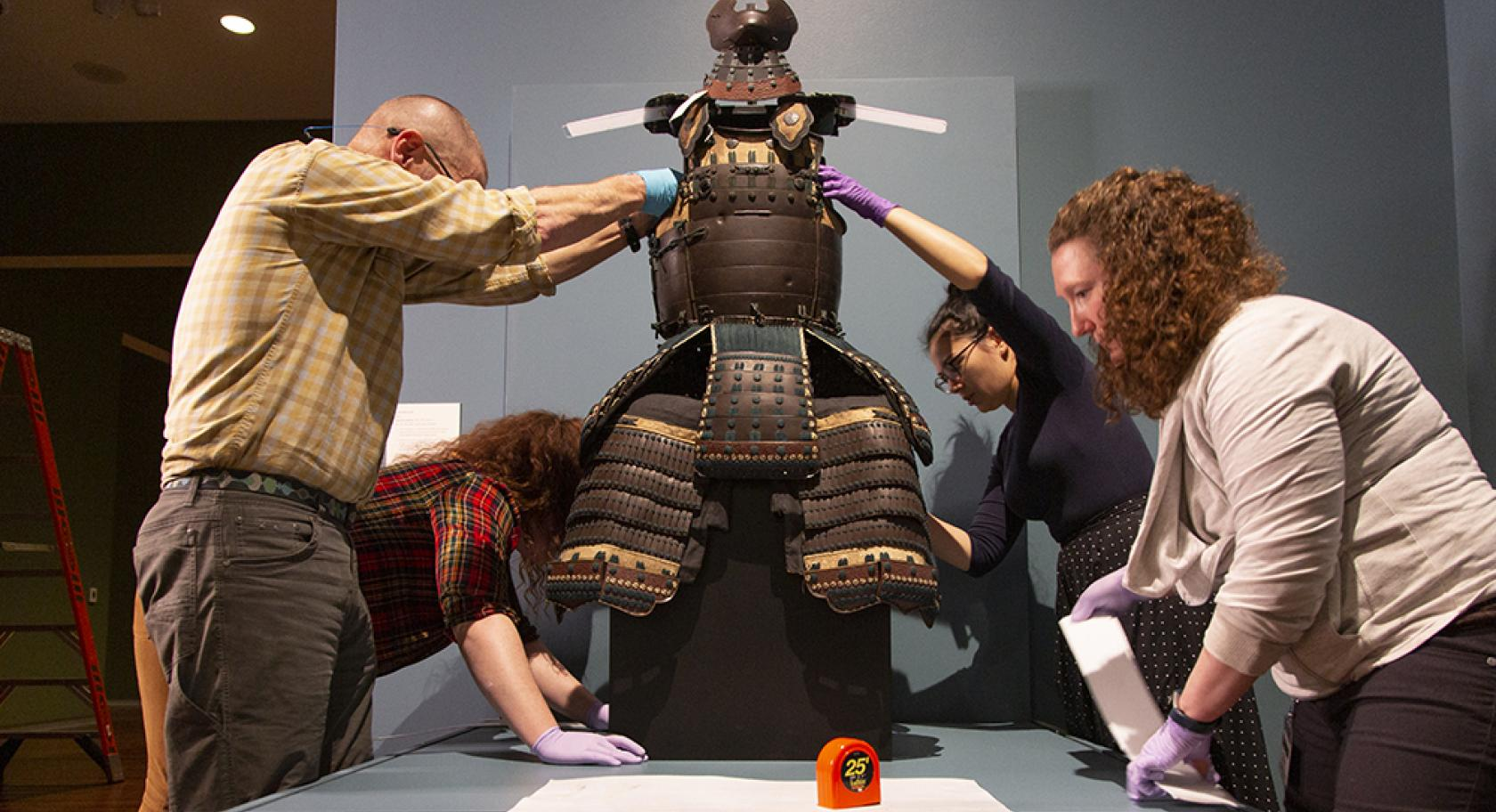 Museum staff install Samurai Armor from Edo Period Japan for Beyond the Divide at the Utah Museum of Fine Arts.