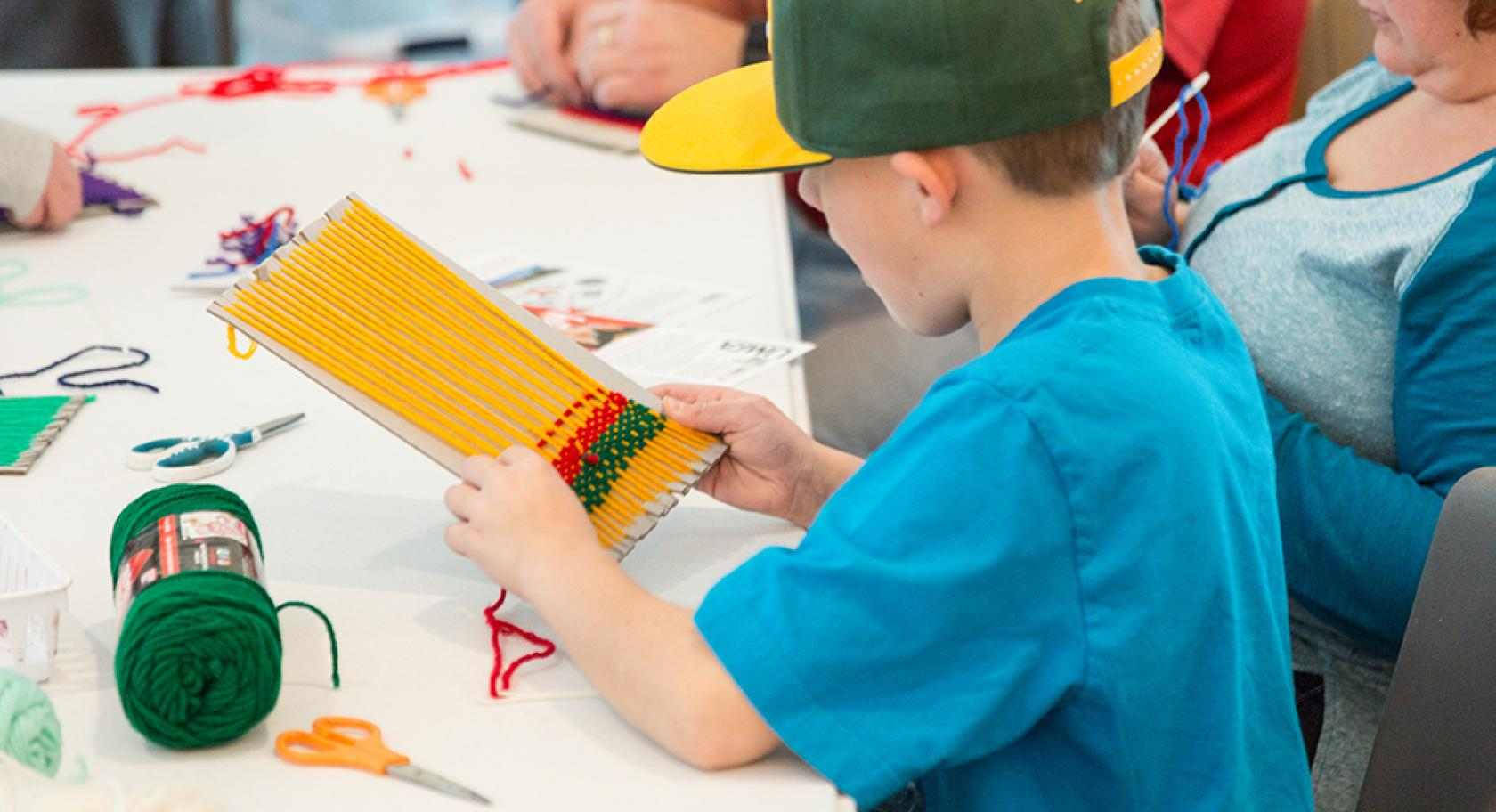 Boy in blue shirt and green and yellow baseball hat weaving a matching opt holder on cardboard loom