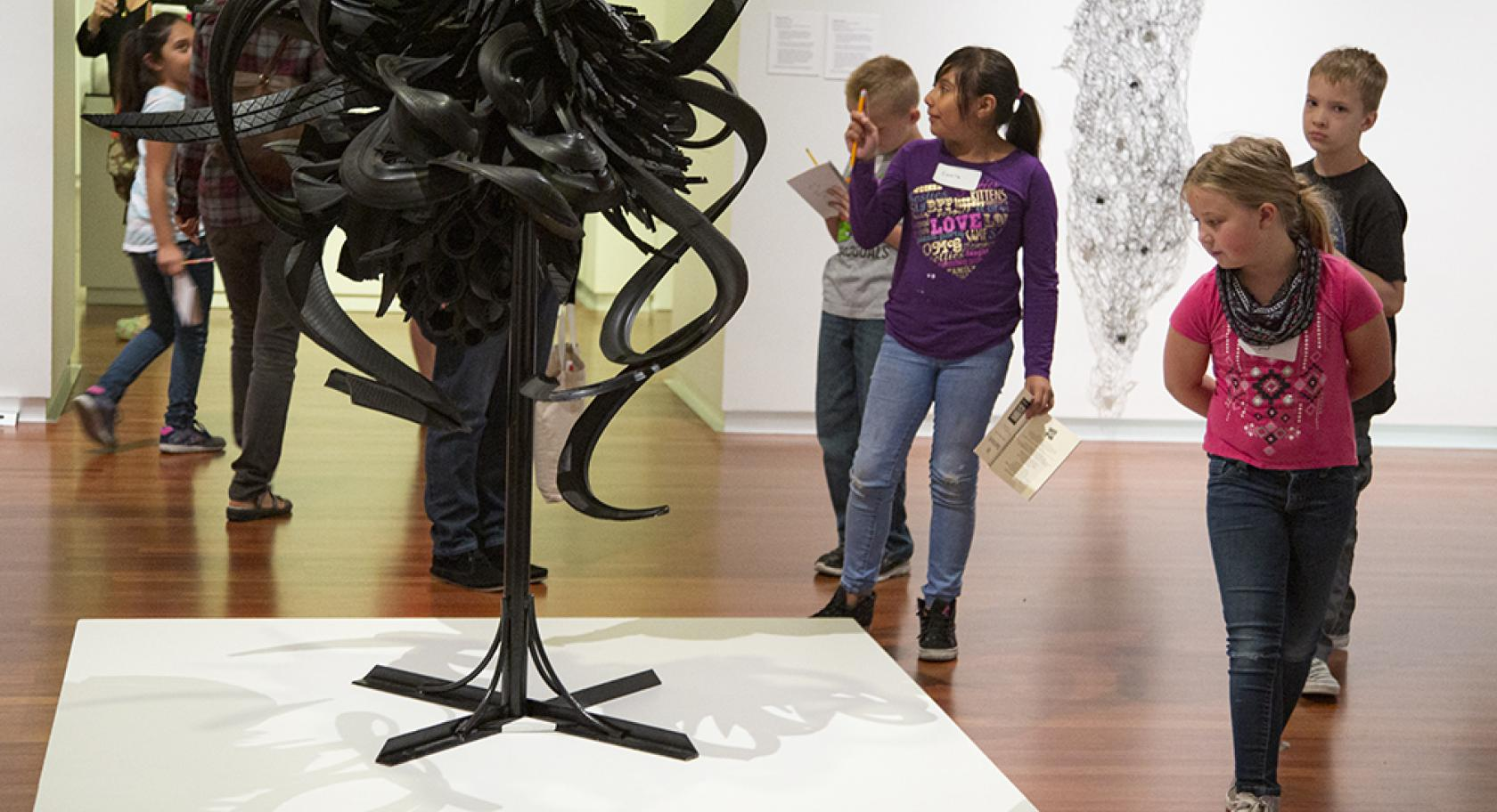 Children looking at Chakaia Booker's Discarded Memories at the Utah Museum of FIne Arts.