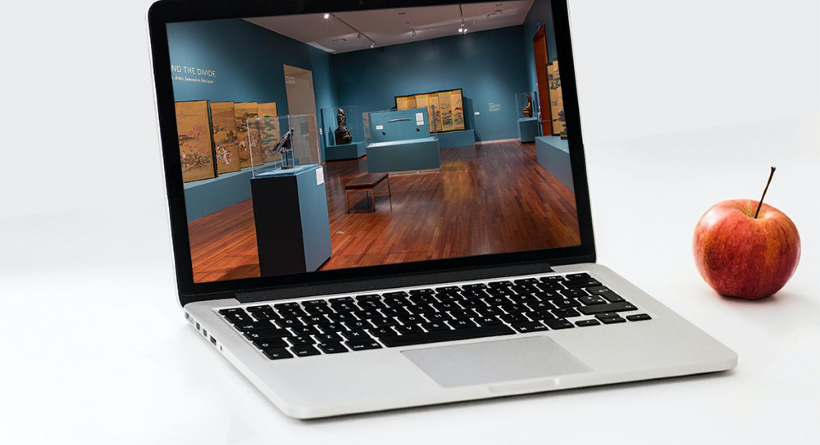 Laptop  on a white backgound with an image of UMFA Beyond the Divide gallery on the screen, an apple sits next to the laptop