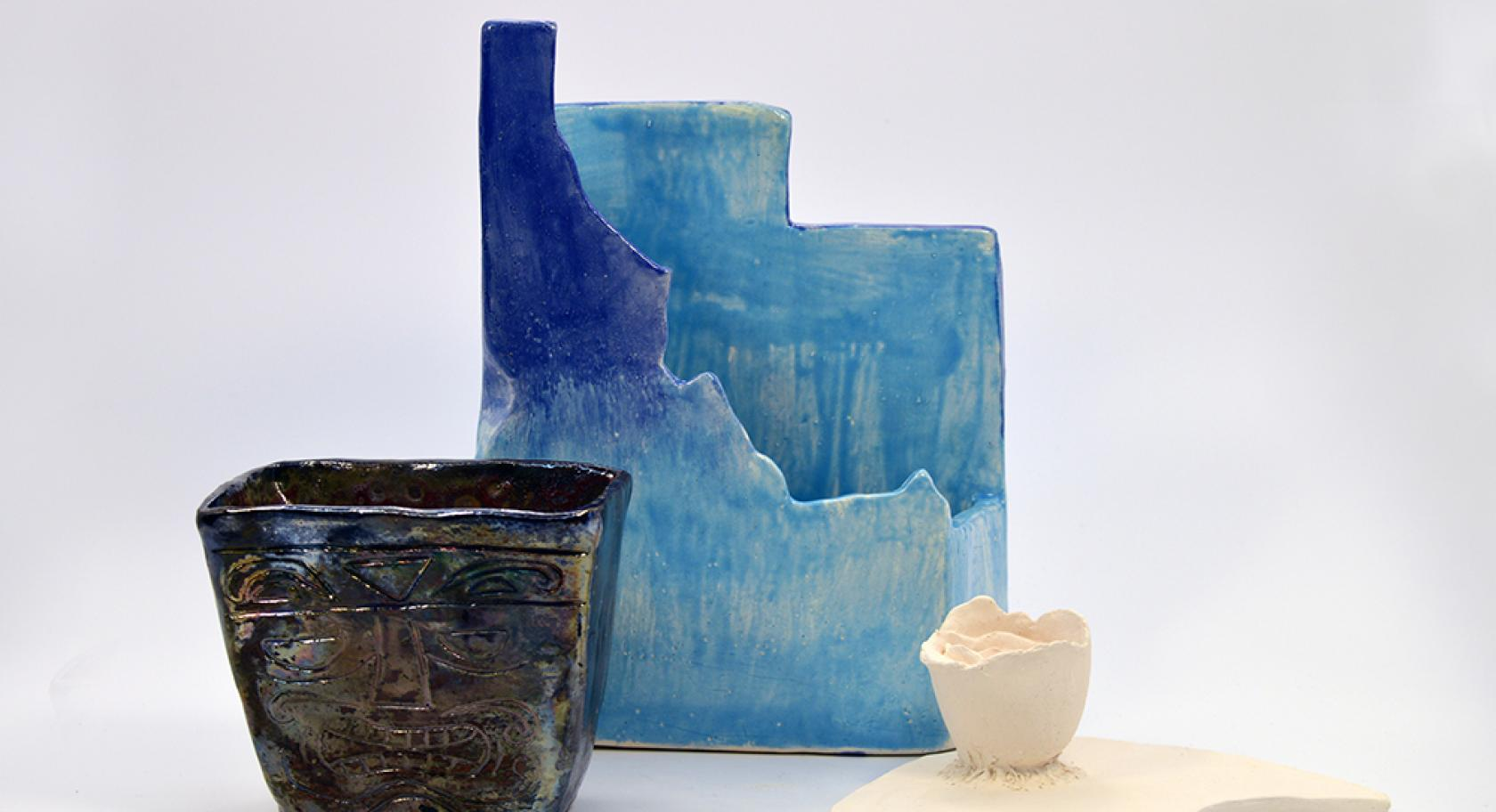 Identity by Zoe Hoopes, Leilani Zamora and Kalayee Hokum, three ceramic object, square black vase, blue vessel Idaho and Utah state shapes, white crescent with small white cup attached