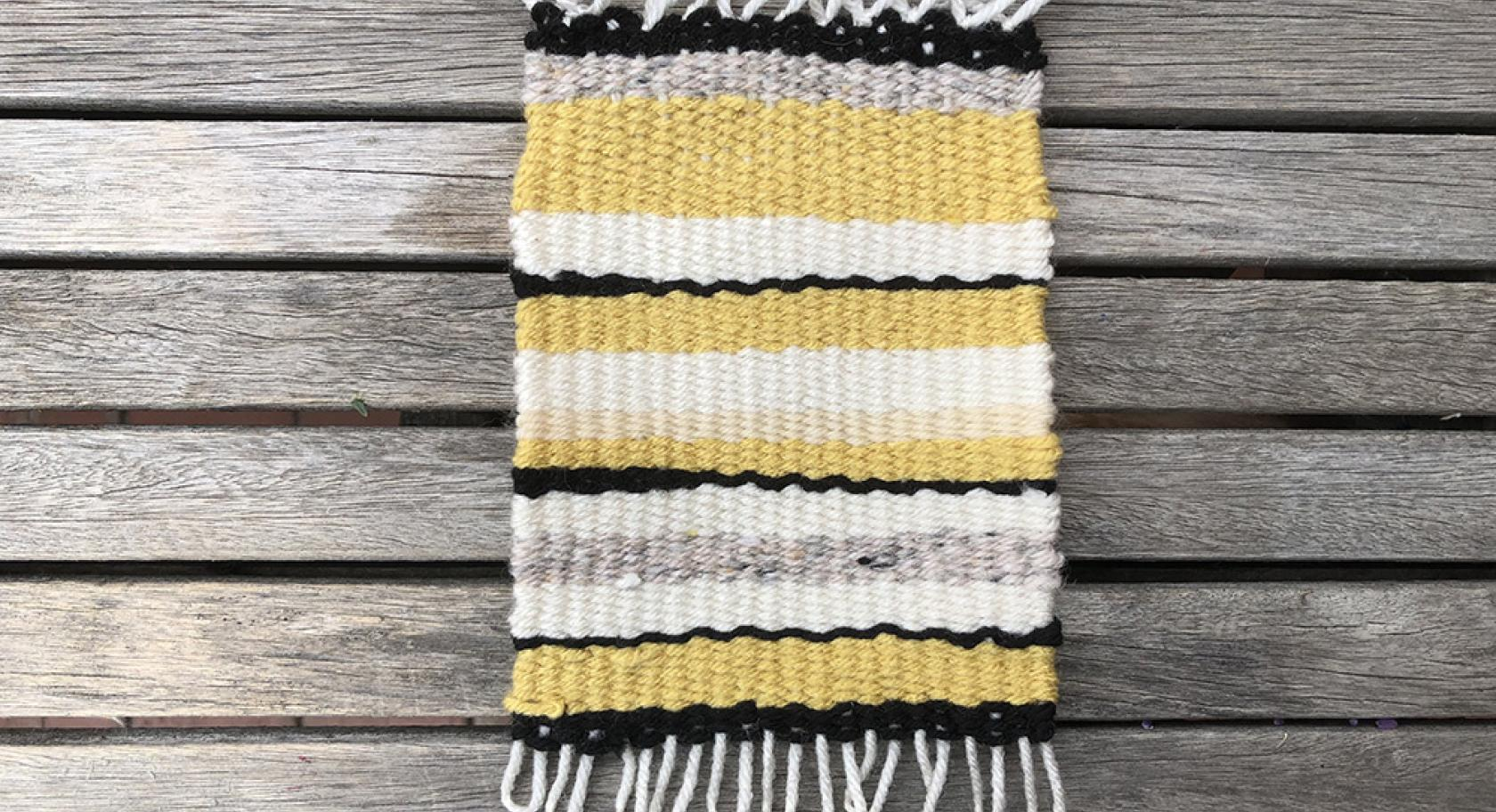 Handmade woven rug made with yellow, gray, white, and black yarn