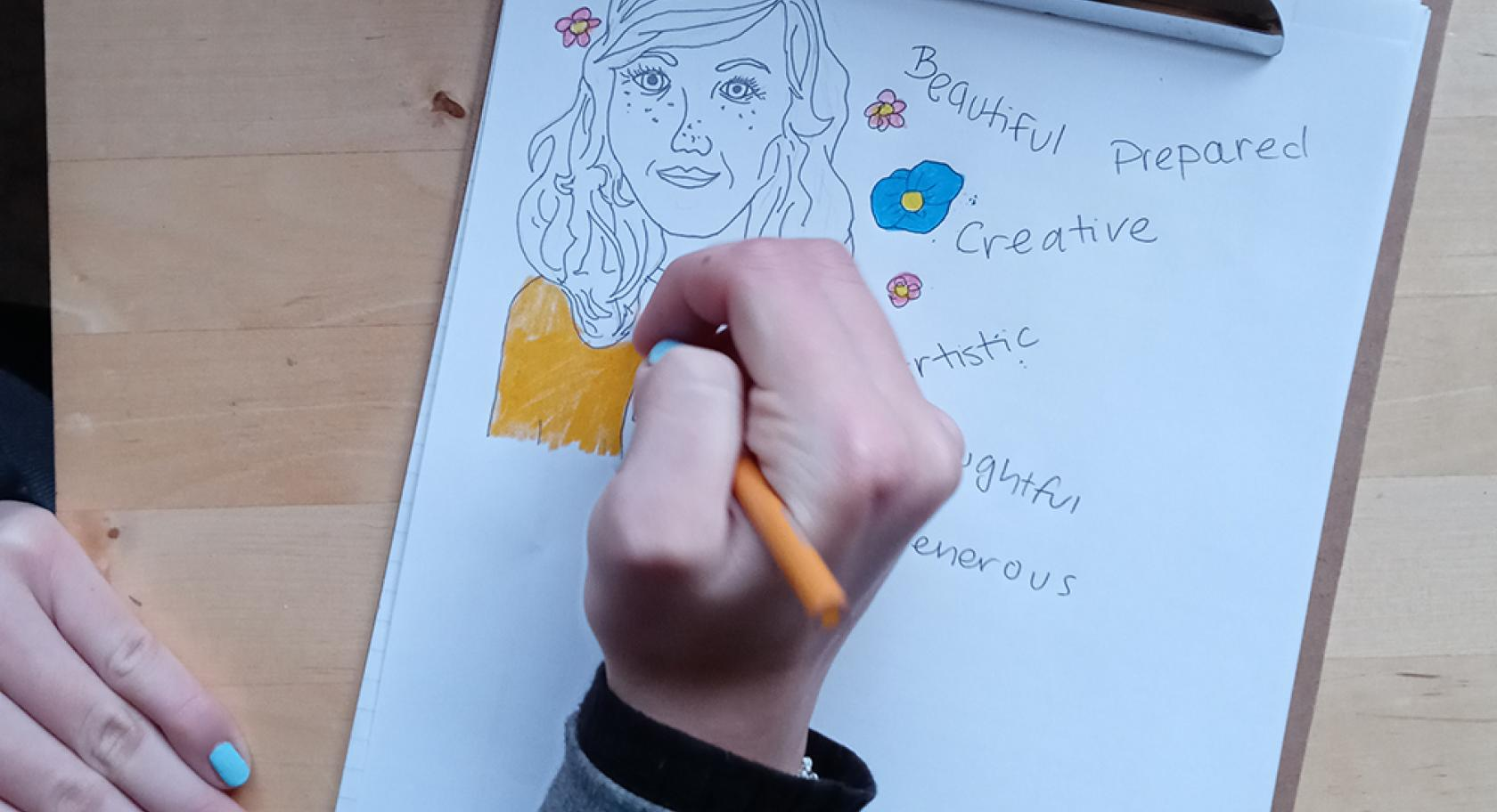 a child's hand holds a yellow pencil drawing on a clipboard. A white piece of paper has a drawing of a black outline of a girl only the shirt is colored yellow