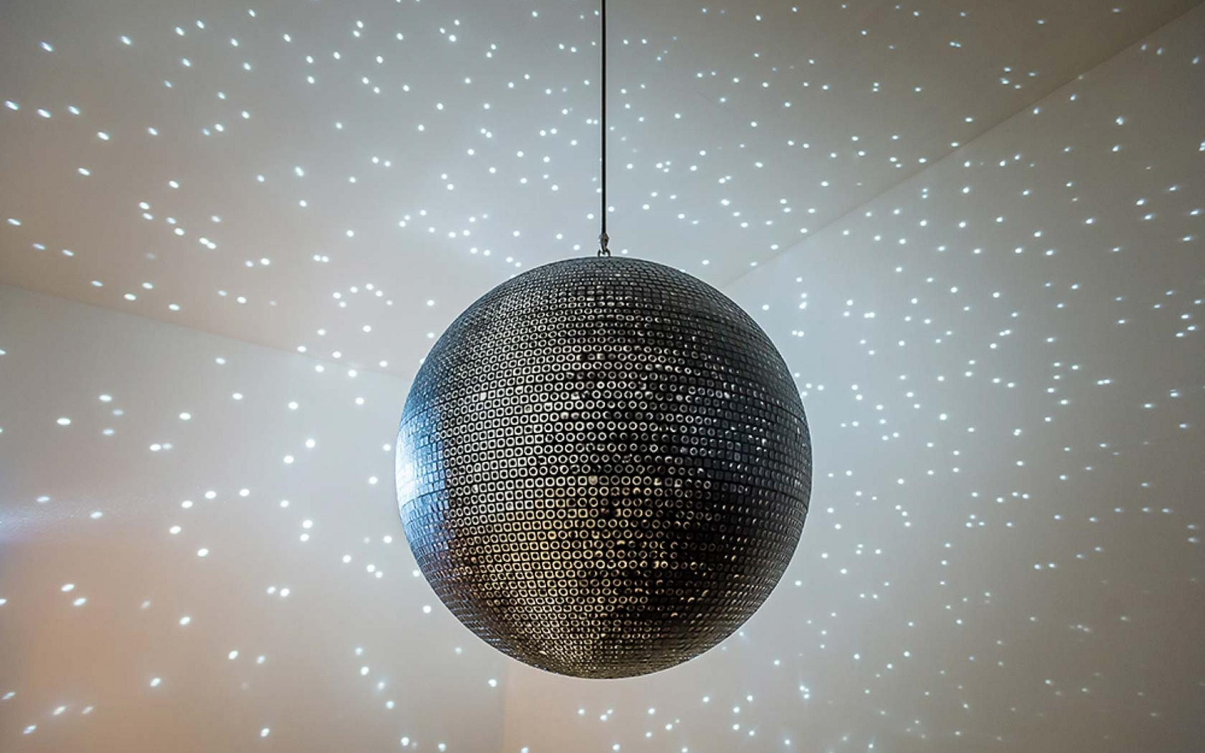 Katie Paterson (Scottish, born 1981), Totality, 2016, printed mirrorball, motor, and lights, 85 cm in diameter, photo © Ben Blackall, courtesy of the Lowry