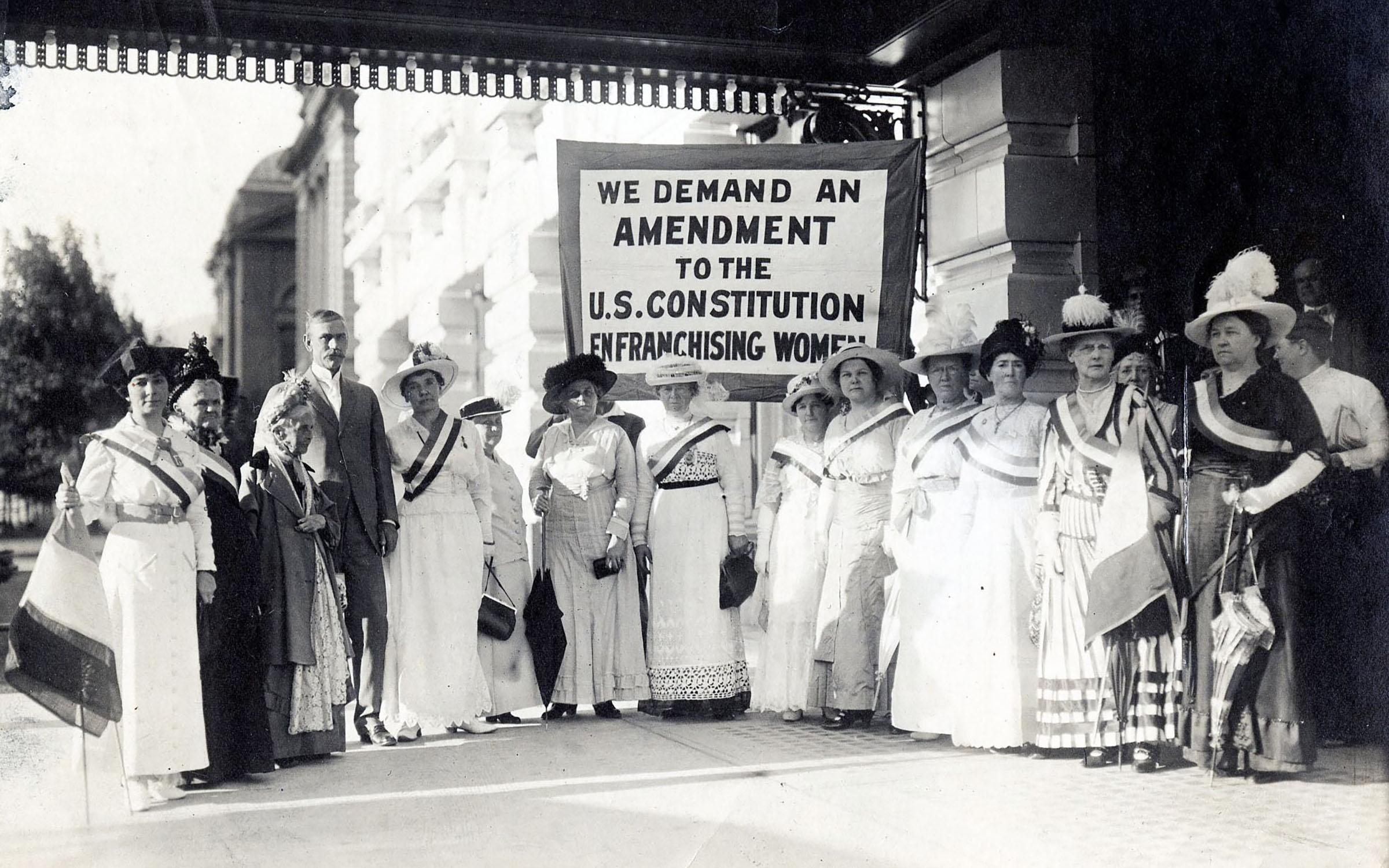 Susan B. Anthony stands with a group of  Women Suffrage Leaders in a group in front of Hotel Utah in 1915 behind the groups a banner reads We demand an amendment to the US Constitution Enfranchising Women.