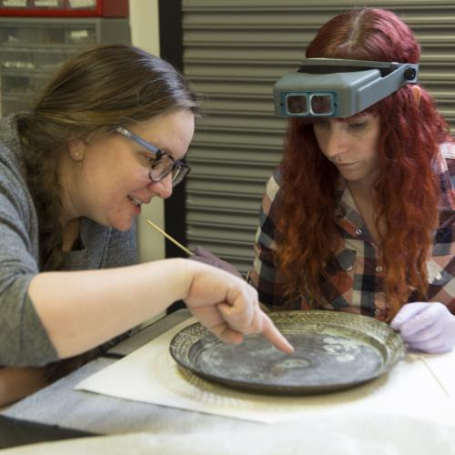 Conservator Robyn Haynie works with IMLS intern Rebekah Abbot to asses a 500-year-old Chinese gong.