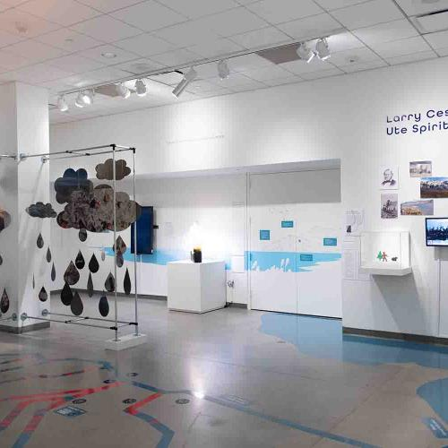Confluence gallery, white room with blue vinyl map of rivers and a lake in the floor a metal cloud sculpture on the left with a wall of landscape images on the right